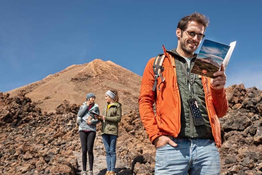 Gars qui est en train de lire le guide des sentiers et filles au fond qui sont en train d'utiliser l'audioguide du Téléphérique