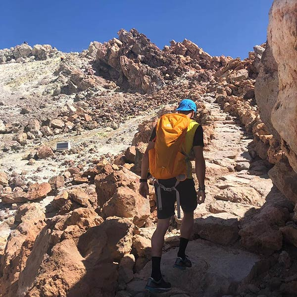 Молодой человек поднимается по тропинке к кратеру Тейде