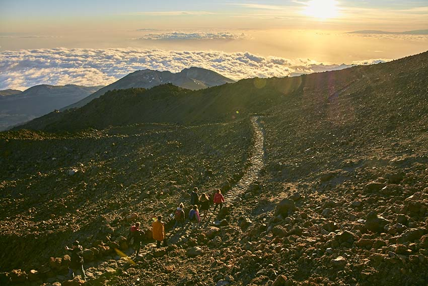 Personas caminando por un sendero del Teide hacia la puesta de sol